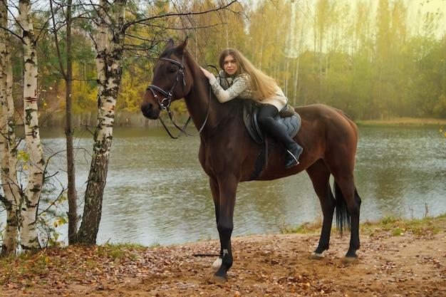 Cute młoda kobieta na koniu w jesiennym lesie nad jeziorem. kobieta jeździec prowadzi konia w parku w niesprzyjającą pochmurną pogodę z deszczem. koncepcja jazdy na świeżym powietrzu, sportu i rekreacji. skopiuj miejsce