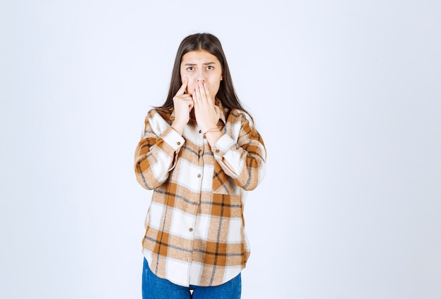 Cute młoda kobieta stojąc na białej ścianie.