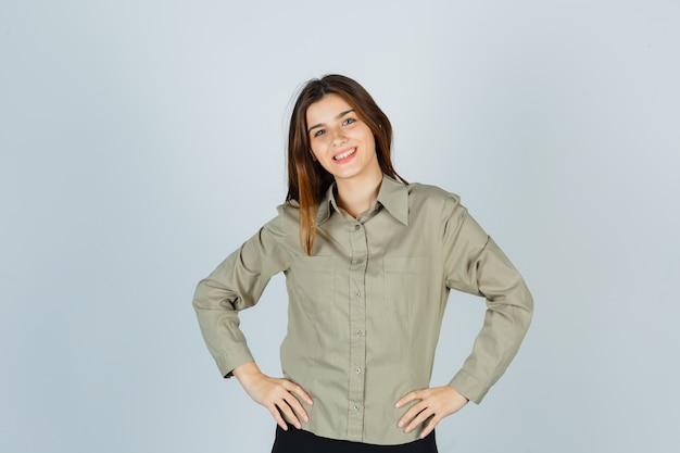 Cute młoda kobieta trzymając się za ręce w pasie w koszuli i patrząc wesoło. przedni widok.