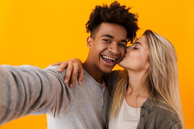 Cute młoda para kochających pozowanie na białym tle nad żółtą ścianą przytulanie, robienie selfie aparatem i całowanie