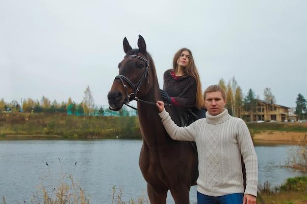 Cute młoda para na koniu w jesiennym lesie nad jeziorem. jeździec kobieta i mężczyzna trzyma konia w parku w niesprzyjającej pochmurnej pogodzie z deszczem. koncepcja jazdy na świeżym powietrzu, sportu i rekreacji. skopiuj miejsce