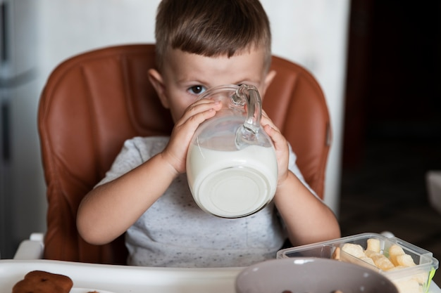 Cute młody chłopak pije mleko
