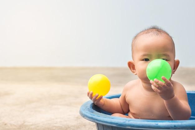Cute new born baby grający w piłkę w plastikowej misce podczas prysznica