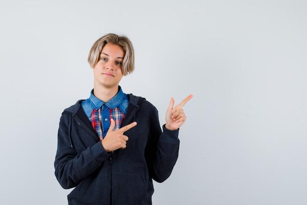 Cute teen boy, wskazując w prawym górnym rogu w koszulę, bluzę z kapturem i patrząc pozytywnie. przedni widok.