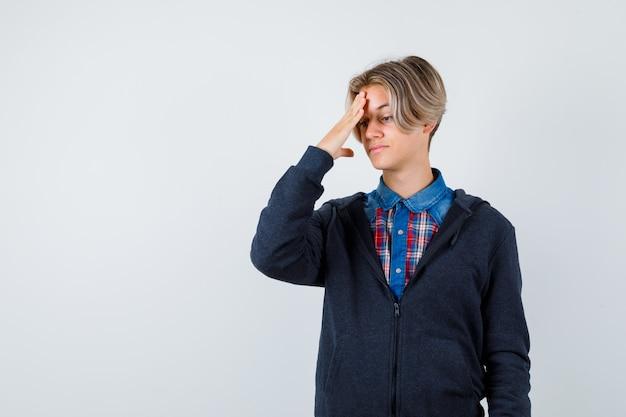 Cute teen chłopiec cierpi na ból głowy w koszuli, bluzie z kapturem i wygląda na zdenerwowanego. przedni widok.