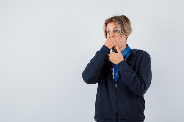 Cute teen chłopiec trzymając rękę na ustach w koszuli, bluzie z kapturem i patrząc przestraszony. przedni widok.