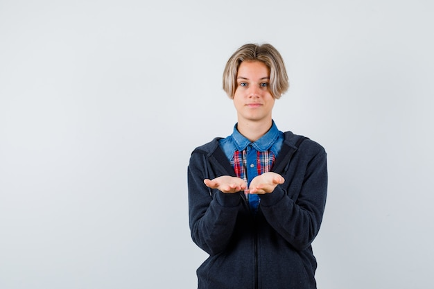 Cute teen chłopiec w koszuli, bluza z kapturem pokazująca odbieranie lub dawanie gestów i patrząc delikatnie, widok z przodu.