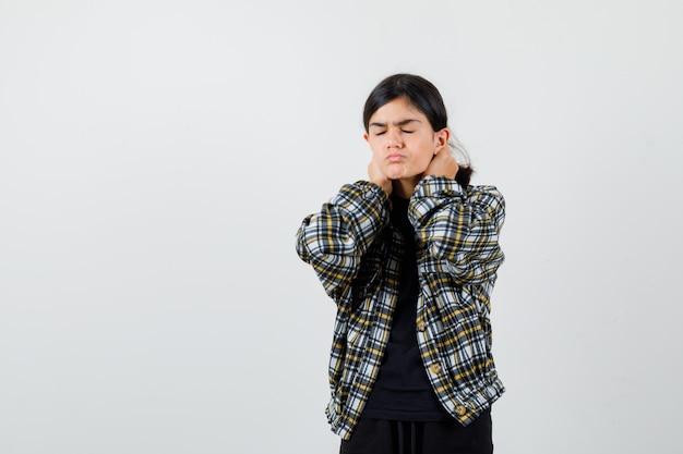 Cute teen dziewczyna trzyma nici na szyi w kraciaste koszule i wygląda na zmęczoną. przedni widok.