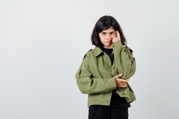 Cute teen dziewczyna trzyma palec na skroniach w zielonej kurtce i wygląda inteligentnie, widok z przodu.