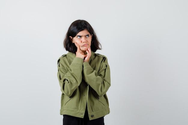 Cute teen dziewczyna trzymając palec na policzku, dotykając podbródka, odwracając wzrok w zielonej kurtce i patrząc zaniepokojony, widok z przodu.
