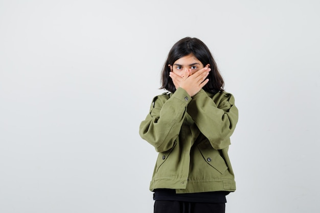 Cute teen dziewczyna trzymając ręce na ustach w zielonej kurtce i patrząc przestraszony, widok z przodu.