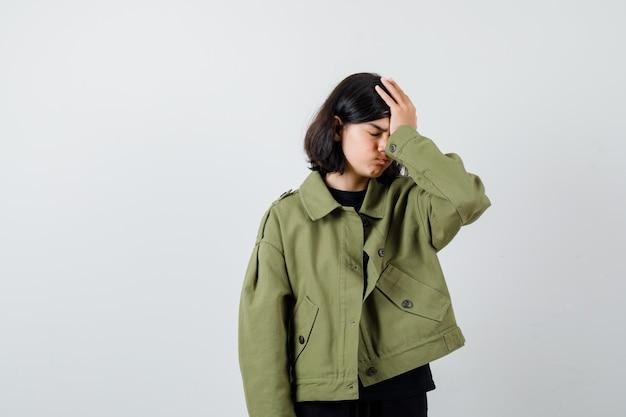 Cute teen dziewczyna trzymając rękę na głowie w zielonej kurtce i patrząc na zmęczony, widok z przodu.