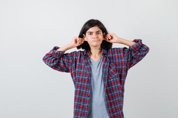 Cute teen dziewczyna w kraciastej koszuli ciągnąc w dół jej płatki uszu i patrząc niezadowolony, widok z przodu.