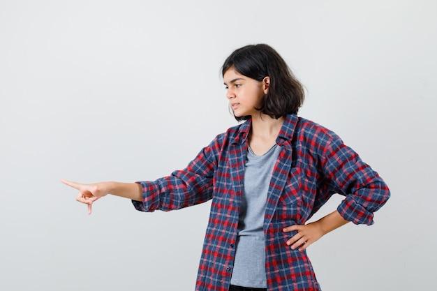 Cute teen dziewczyna w kraciastej koszuli, wskazując w lewo i patrząc skupiony, widok z przodu.