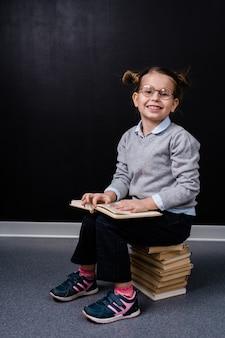 Cute uśmiechnięta uczennica siedzi na stosie książek podczas czytania jednego z nich na tablicy w izolacji
