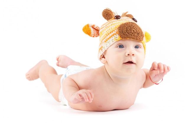 Cutie mały chłopiec w białej pieluszce i czapce jelenia