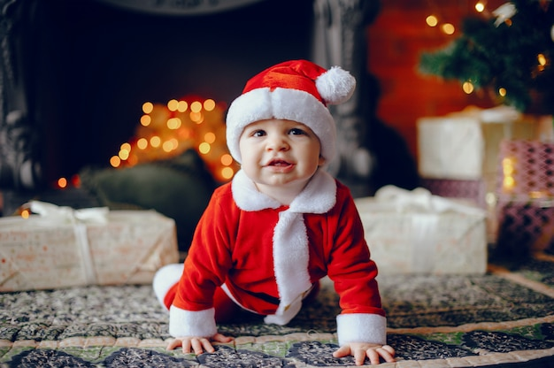 Cutte mały chłopiec w domu w pobliżu ozdób choinkowych