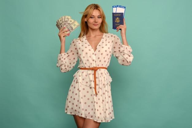 Cuty młoda kobieta trzyma bilety z paszportem i pieniądze doller na niebieskim tle studio