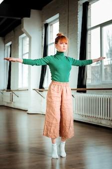 Ćwicz dla równowagi. pretty rudowłosa dziewczyna ubrana w pomarańczowe spodnie patrząc skupiony podczas wykonywania ćwiczeń równoważących