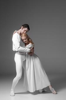 Ćwiczenia dwóch młodych tancerzy baletowych. atrakcyjnych wykonawców tańca w kolorze białym