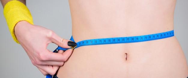 Ćwiczenia fitness spalające kalorie. utrata wagi. fitness i zdrowie. kobiecy wąski brzuch i taśma miernicza. trening trenera fitness sportowca. próbuję schudnąć. przygotuj letnie ciało. wynik sprawności.