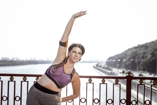 Ćwiczenia fizyczne. ładna aktywna kobieta, trzymając ją za rękę podczas ćwiczeń fizycznych