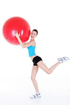 Ćwiczenia fizyczne z fitballem w wykonaniu młodej pięknej dziewczyny