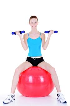 Ćwiczenia fizyczne z hantlami i fitball dla młodej kobiety - na białym tle