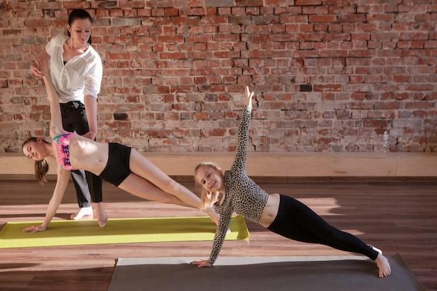 Ćwiczenia gimnastyczne. zdrowy styl życia dzieci. nastoletni sport z instruktorką, joga dla dzieci. szczęśliwe dziewczyny rozciągające w studio. tło ściany siłowni z wolną przestrzenią, koncepcja zdrowia