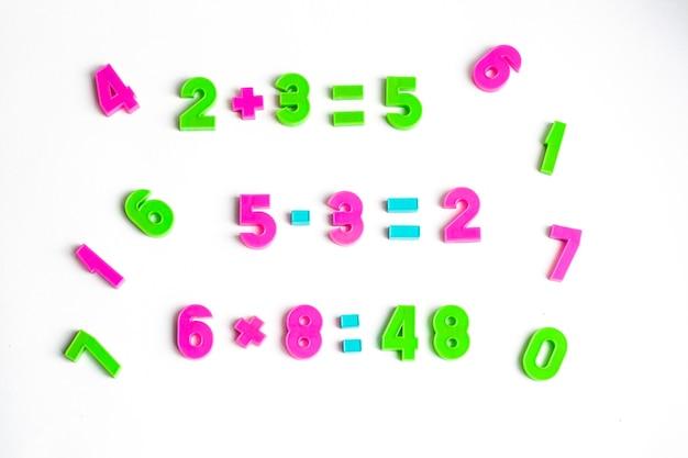 Ćwiczenia matematyczne i cyfry na białym tle
