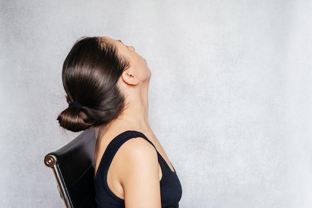 Ćwiczenia metodą mckenzie łagodzące ból szyi, kobieta delikatnie obraca głowę podczas wykonywania ćwiczeń przeciwbólowych szyi