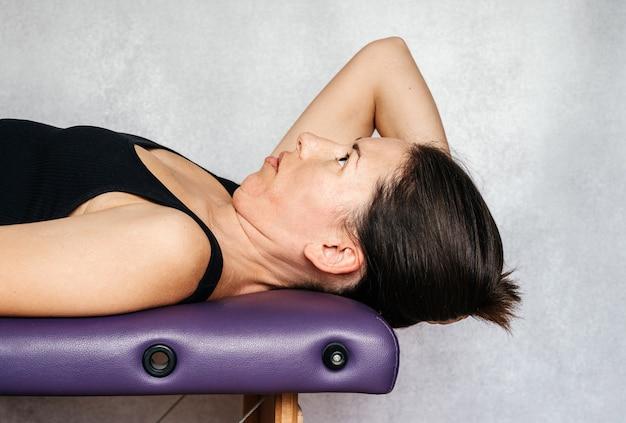 Ćwiczenia metodą mckenzie łagodzące ból szyi, kobieta leżąca na stole do masażu i opuszczająca głowę w kierunku podłogi podczas wykonywania ćwiczeń przeciwbólowych szyi