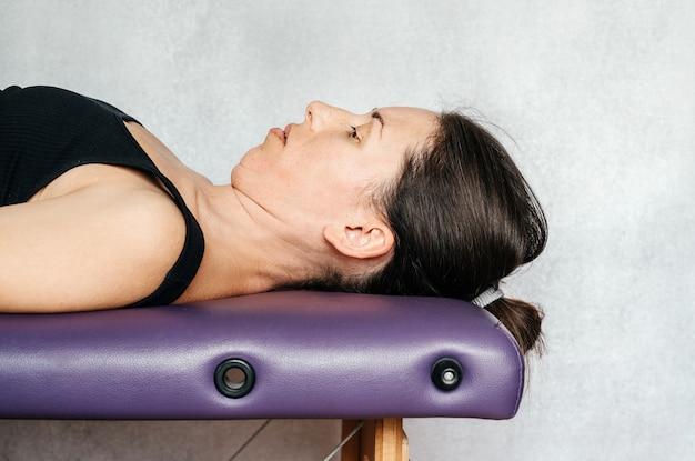 Ćwiczenia metodą mckenzie łagodzące ból szyi, kobieta leżąca na stole do masażu i wpychająca głowę do stołu i podciągająca podbródek podczas wykonywania ćwiczeń przeciwbólowych szyi