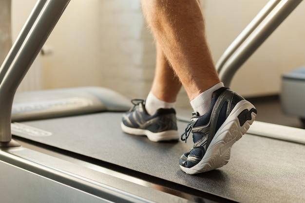 Ćwiczenia na bieżni. zbliżenie: mężczyzna chodzący na bieżni w klubie sportowym