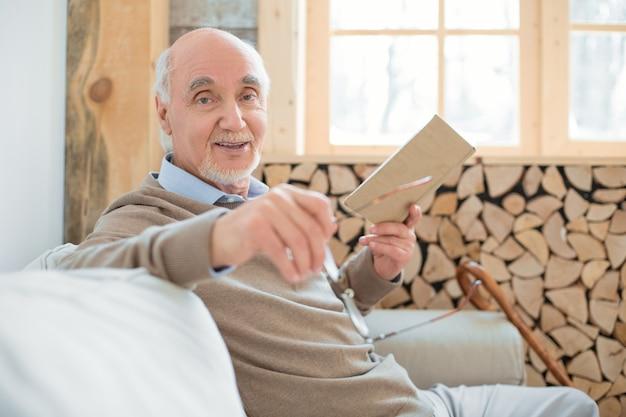 Ćwiczenia na mózg. radosny wesoły starszy mężczyzna siedzi na kanapie, trzymając okulary i czytając książkę