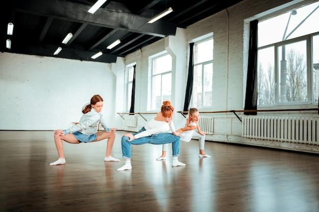 Ćwiczenia na ramiona. szczupła, piękna nauczycielka baletu z rudymi włosami wyglądająca na zaangażowaną, pokazująca uczniom ruchy ramion