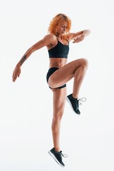 Ćwiczenia. redhead kobieta kulturysta jest w studio na białej przestrzeni.