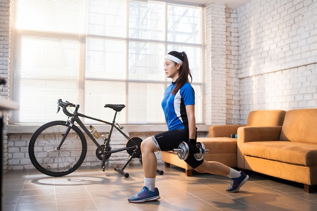 Ćwiczenia rowerzysty z nogą rzucają się. ona jest w domu.