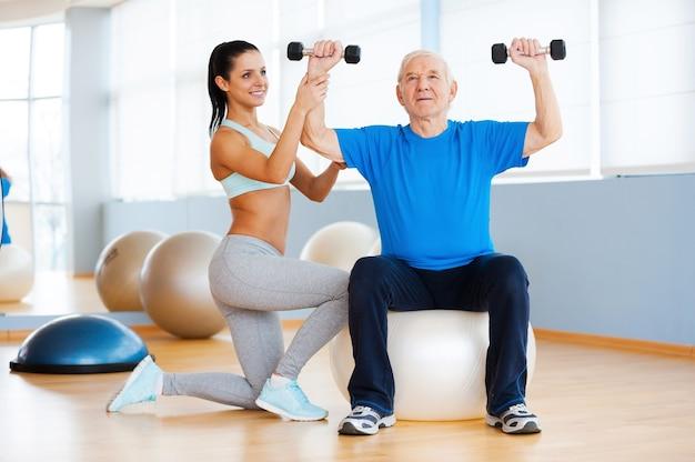 Ćwiczenia siłowe. pewna siebie fizjoterapeutka pracująca ze starszym mężczyzną w klubie fitness