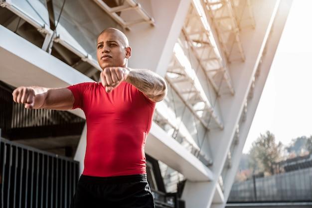 Ćwiczenia sportowe. przystojny, młody człowiek, trzymając się za ręce przed nim podczas wykonywania ćwiczeń fizycznych
