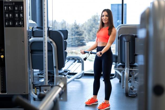 Ćwiczenia w symulatorze bloku. przedłużenie bicepsa. kobieta lekkoatletycznego treningu w siłowni