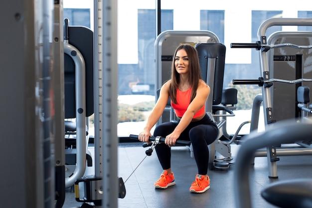 Ćwiczenia w symulatorze bloku. rozszerzenie bicepsa. kobieta lekkoatletycznego treningu w siłowni