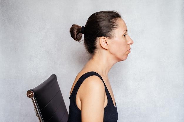 Ćwiczenie metodą mckenzie w celu złagodzenia bólu szyi, kobieta trzyma głowę w pozycji cofniętej podczas wykonywania ćwiczeń przeciwbólowych szyi