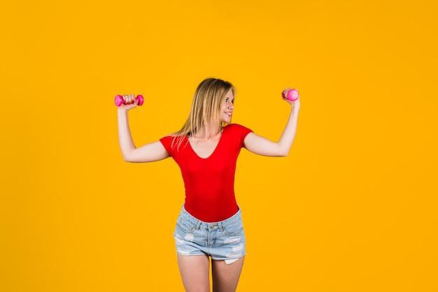 Ćwiczenie na ramiona kobieta ćwicząca z hantlami fitness kobieta trzymająca siłę hantli i