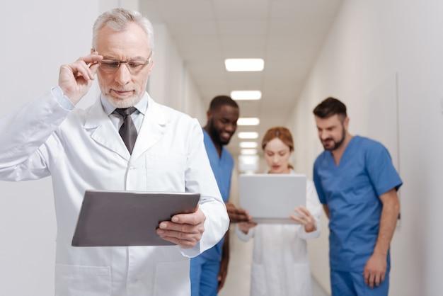 Ćwiczenie nowego podejścia. starszy, brodaty, zaangażowany pediatra, cieszy się pracą w klinice i pracuje z tabletem, podczas gdy inni koledzy korzystają z laptopa w tle