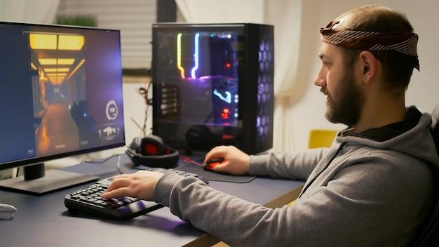 Cyber gracz grający w e-sportową strzelankę do wirtualnego turnieju na potężnym komputerze za pomocą klawiatury rgb i profesjonalnej myszy. odtwarzacze strumieniujące gry wideo online w domowym studiu gier.