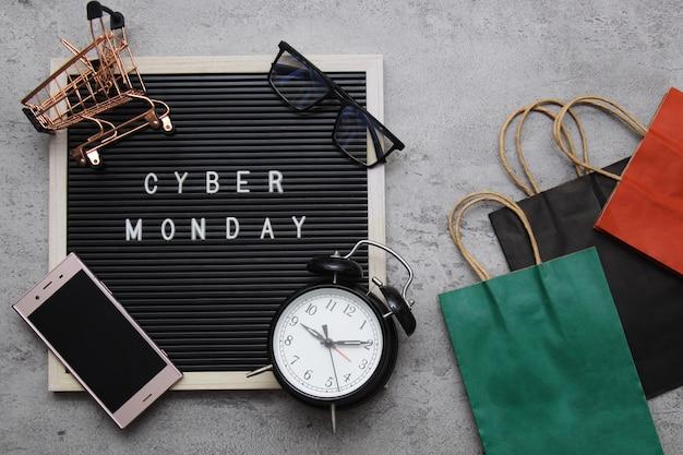 Cyber mondayflat połóż tekst sprzedaży na tablicy z budzikiem, dobrą torbą z gadżetami i gadżetem