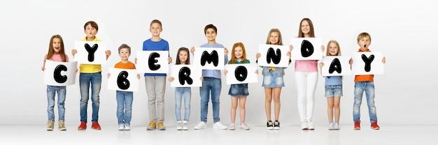 Cyber poniedziałek, koncepcja sprzedaży. grupa dzieci, dzieci i młodzieży w jasnych ubraniach z emocjami szczęścia holdind liter na białym tle. negatywna przestrzeń. kolorowy obraz do twojej reklamy.