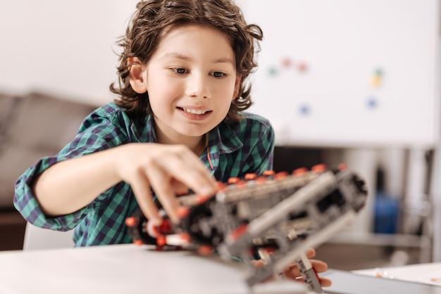 Cyber robot w moich rękach. zadowolony wesoły optymistyczny chłopiec siedzący w klasie i dotykający urządzenia podczas programowania robota