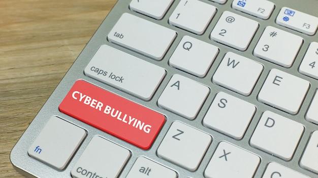 Cyber zastraszanie czerwony przycisk na srebrnej klawiaturze.